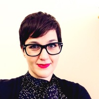 women with dark pixie haircut with large black glasses and bold red lip smiling at camera. She is wearing a black high neck top.