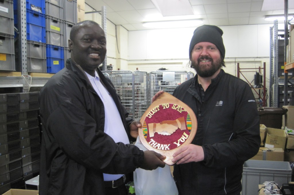 Eddie presents Ross with a plaque from Ghana