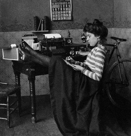 ca. 1900 --- Woman Reclining at Desk Next to Typewriter --- Image by © CORBIS