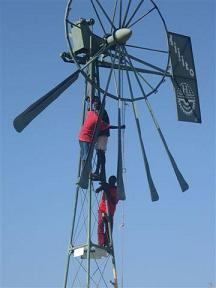 Ileret youth bringing down the old wind pump.