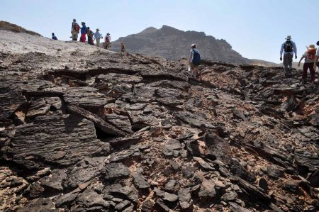 Students climb up black sandstone plates that have crumbled as the result of erosion.