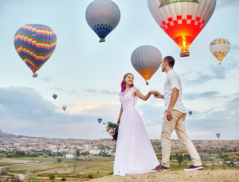 Couple in love stands on background of balloons in Cappadocia.