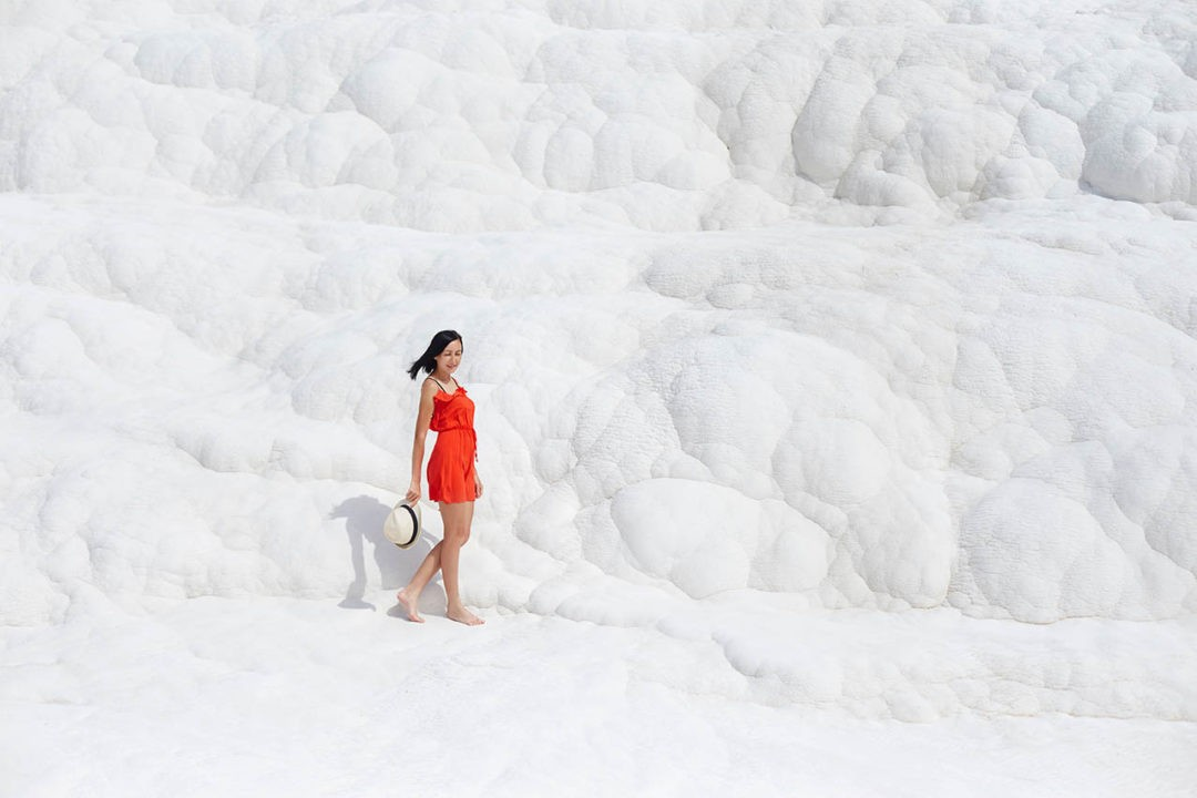 Girl in red dress on white travertines, Pamukkale