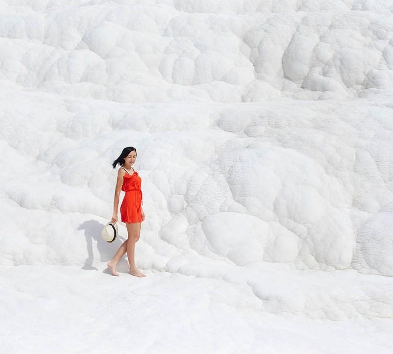 Girl in red dress on white travertines, Pamukkale