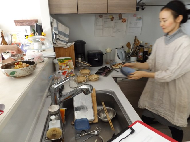 Sensei moving quickly to help get us ready to cook dishes simultaneously. Spy salmon in vinegar in the bowl on the left on the counter.