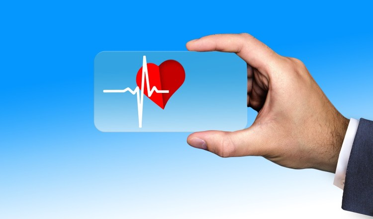 A man's hand holding a credit card size card with a picture of a heart on it and a line showing heart rhythm.