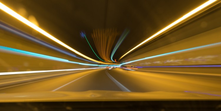 Photo of a tunnel with a road inside and blurred lights, representing travelling with some speed
