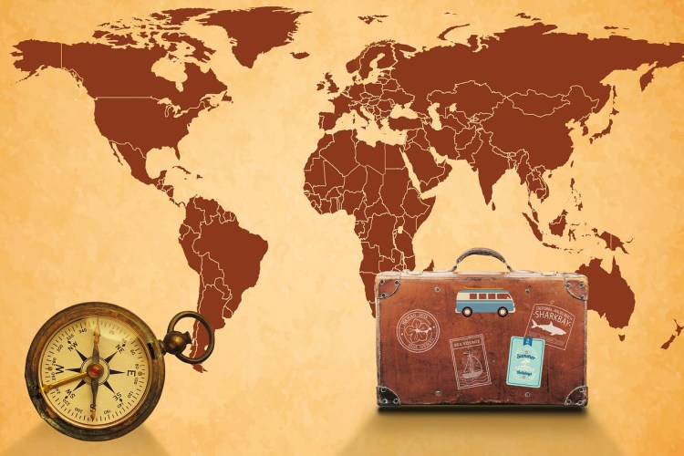 A sepia-toned world map with an old-fashioned compass on the left and an old-fashioned brown suitcase on the right