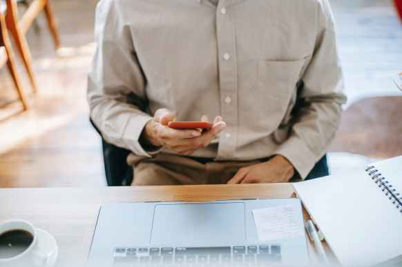 faceless guy freelancer working on netbook in house