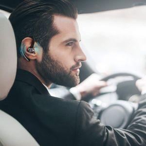 Hombre conduciendo un coche y escuchando música por el auricular