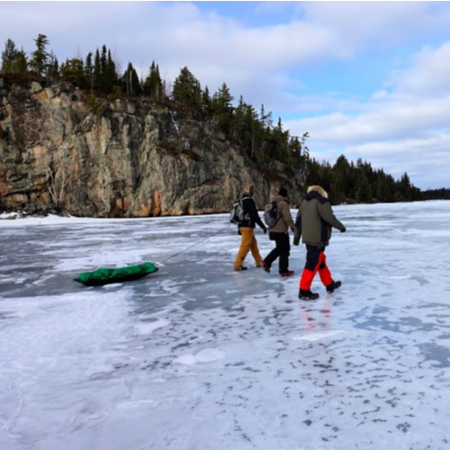 Ice fisherman walk past the Seagull Lake Palisade Cliffs in the Boundary Waters Canoe Area Wilderness