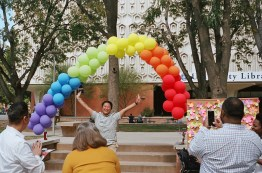 Faculty members cheered and photographed their co-workers as they walked through the rainbow arch.