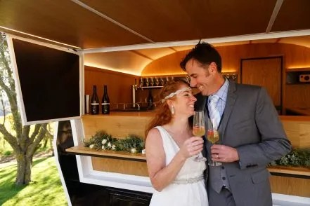 Showing the happy married couple in front of the wine bar caravan