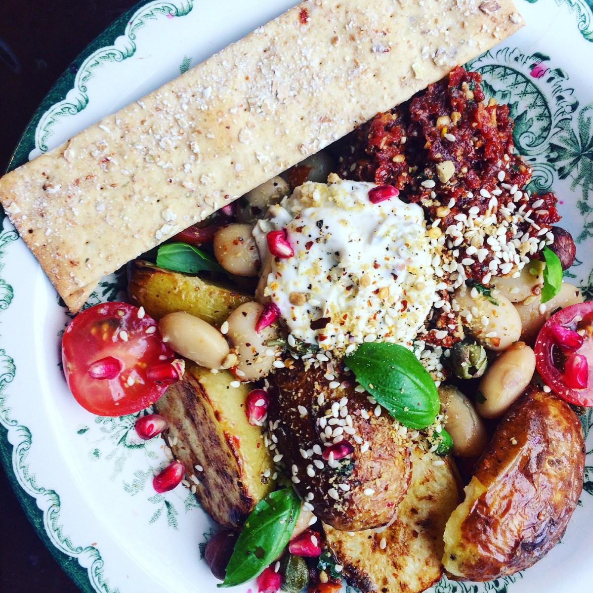 Vegetarisk plocksallad med tomatpesto, rostad potatis, sesamfrön och granatäpple