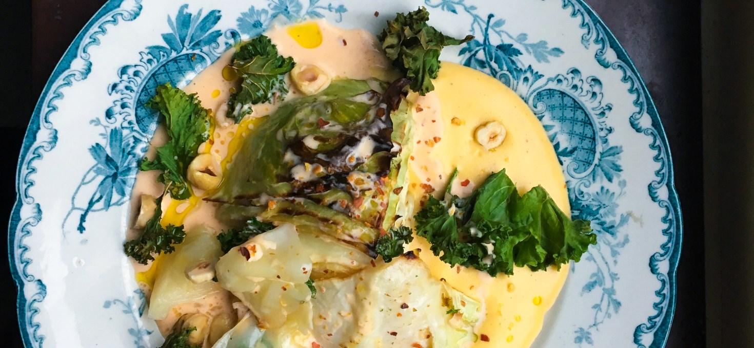 Smörbakad vitkål med harissagrädde, grönkålschips, äggkräm och hasselnötter