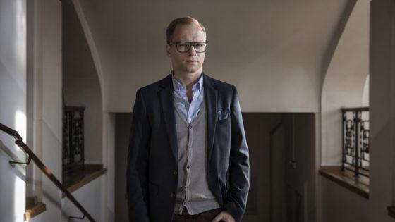 Aktor Maciej Stuhr stoi na korytarzu, ubrany w okulary. Ma na sobie marynarkę i sweter.