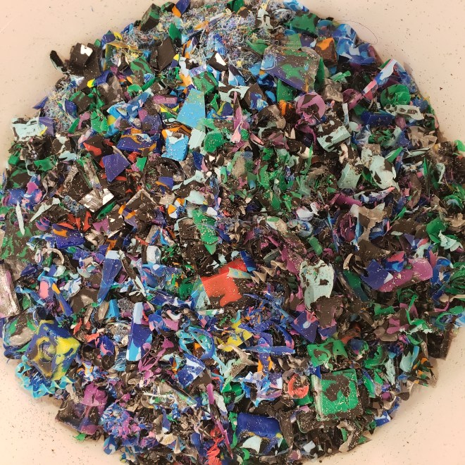Bucket of recycled plastic mistakes and shavings