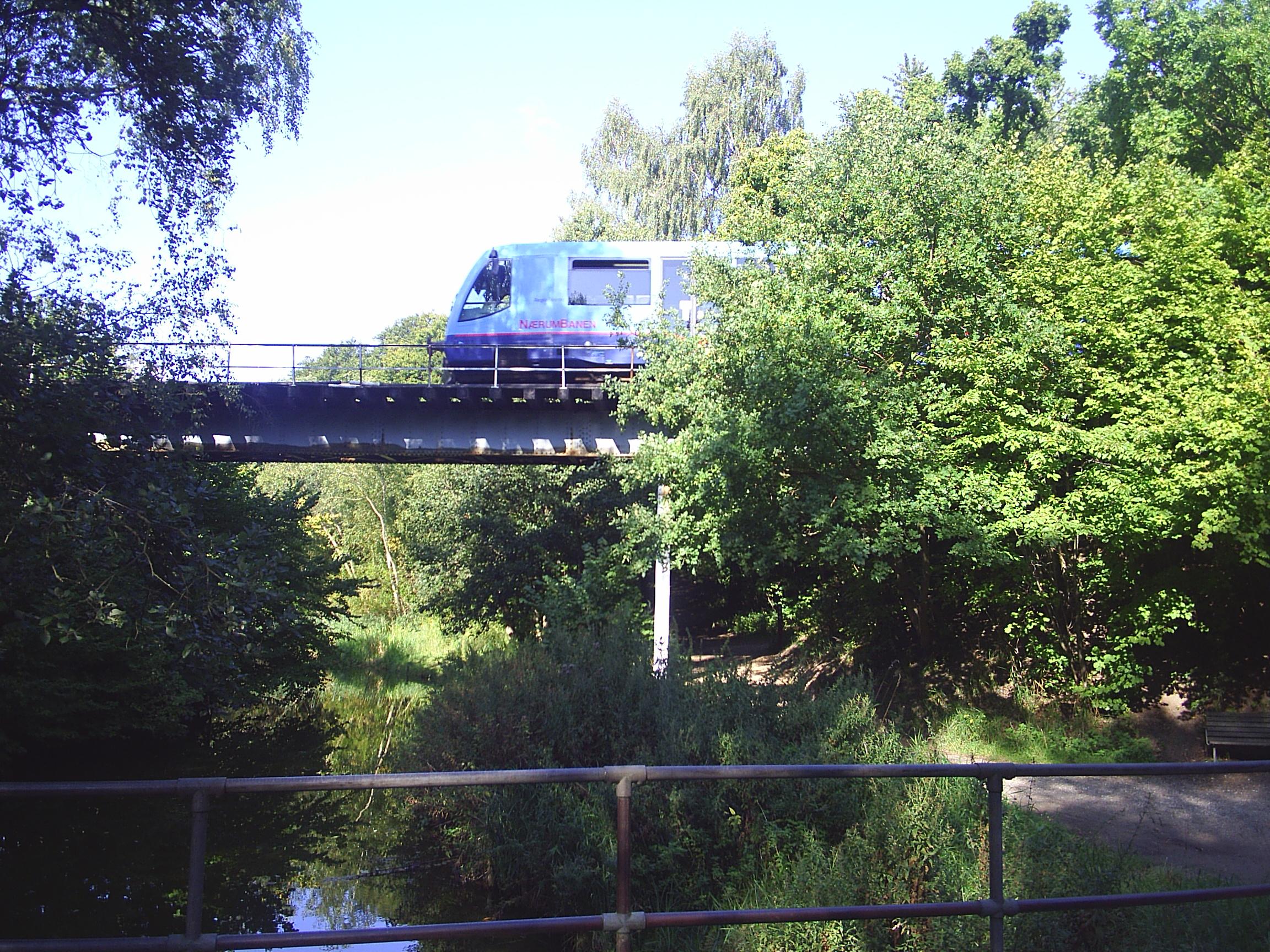 Lokal tog passerer bro over Mølleåen 500 m øst for Ravnholm station. Her er også bro-overgange for tobenede. Foto: sept. 2008