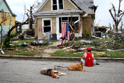 Man with dogs sitting in street staring at his damaged Joplin home