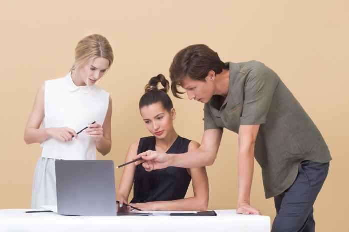 Dvije žene i muškarac gledaju prezentaciju o asertivnosti na prijenosnom računalu