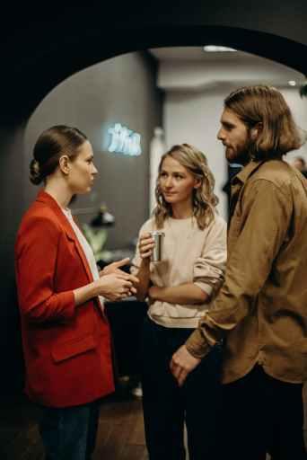 Dvije žene i muškarac stoje i razgovaraju ostavljajući dobar dojam jedno o drugome.