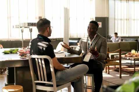 Dvojica muškaraca sjede za stolom i razgovorom ostavljaju dobar dojam jedno od drugome.