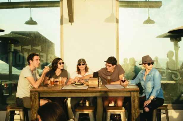 Grupa ljudi koji se međusobno poznaju sjedi za stolom u restoranu.