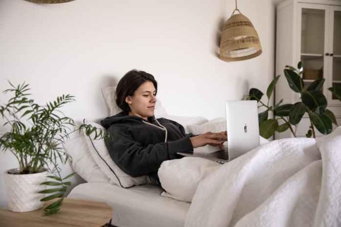 Djevojka u krevetu preko laptopa pregledava svoj profil na dating stranici