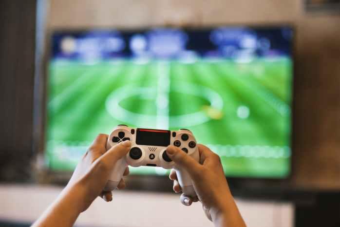 Lijeni čovjek igra video igre na velikom televizoru  i odgađa obaveze
