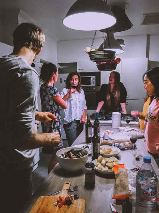 Skup ljudi okupljeni oko stola na kućnoj zabavi. Odlična prilika za upoznati nove prijatelje.