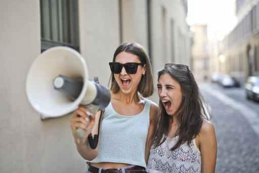 Dvije žene u majicama kratkih rukava stoje na gradskoj ulici i glasno govore u megafon koristeći svoje socijalne vještine.
