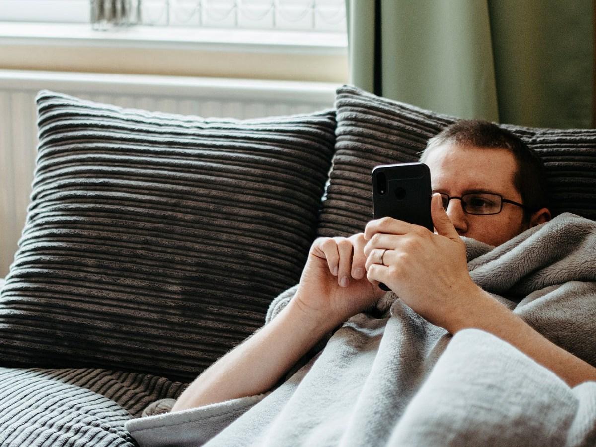 Lijeni muškarac umotan u sivu deku čita poruke na mobitelu