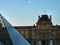 Nearly dusk, the moon shines over the Louvre