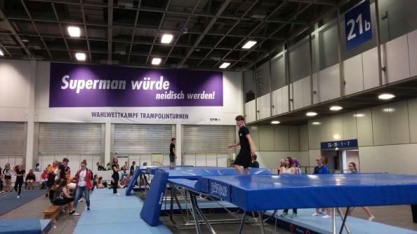 Niklas bei seinem Wahlwettkampf. In der Halle sind Spruchbänder der verschiedenen Sportarten angebracht.