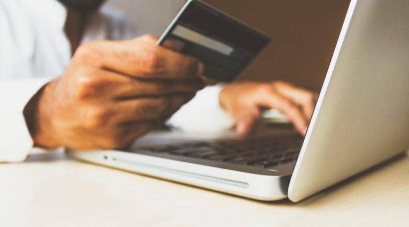 Uma pessoa mexendo em um laptop segura um cartão de crédito na frente.