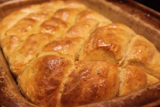 A pan of scored herby pull-apart bread fresh from the oven
