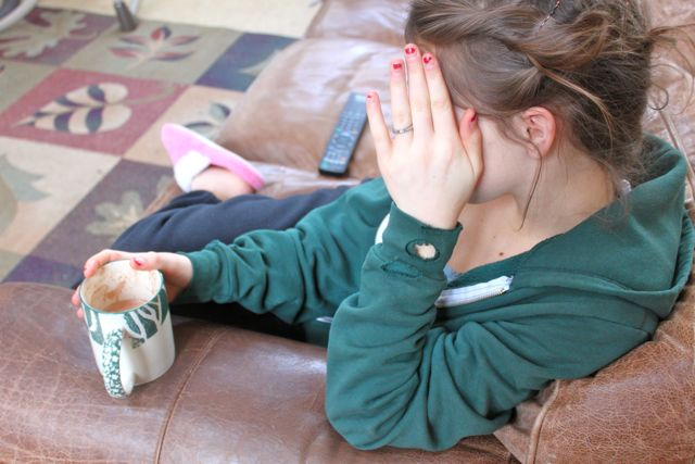 A girl with an empty mug of cocoa hiding her face