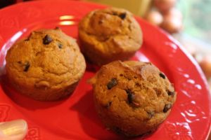 Red plate containing chocolate chip pumpkin muffins