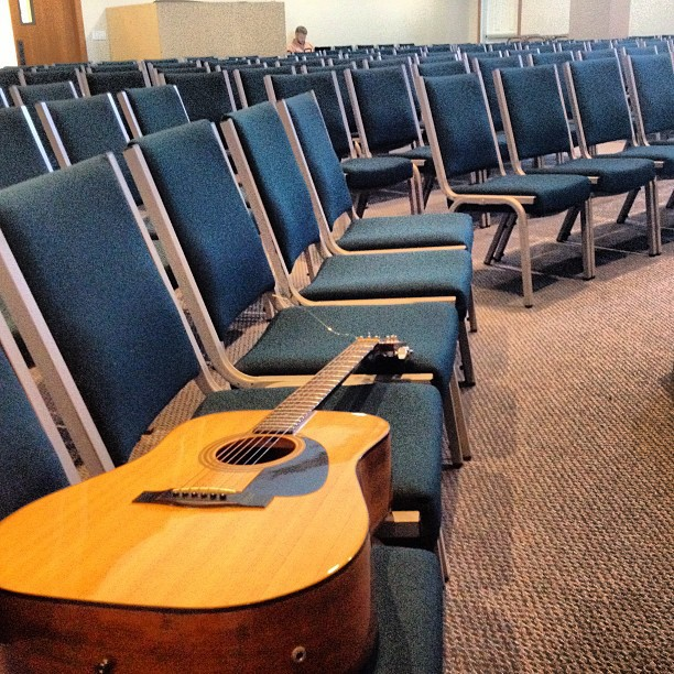 A side view of several rows of chairs with a guitar lying across three of them