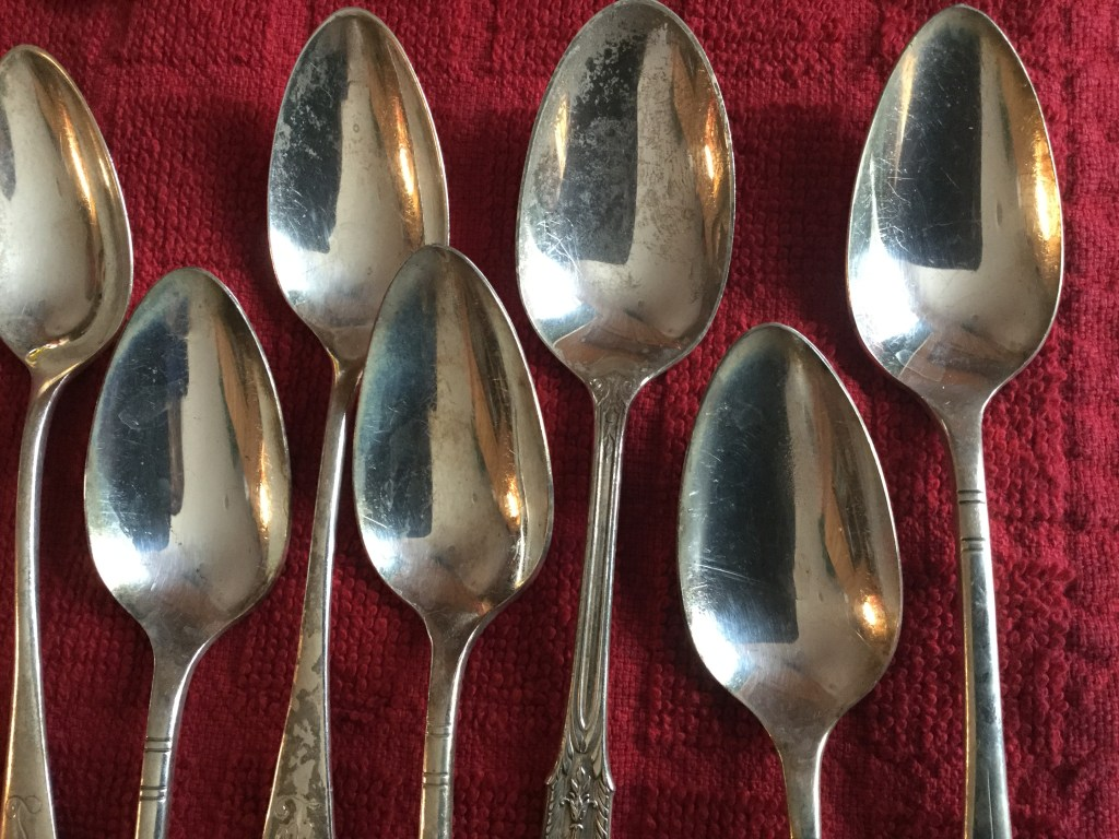 Seven silver spoons laid out on a red cloth