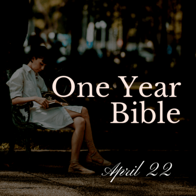 Woman in white dress sitting on bench reading a Bible
