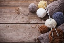 Six earth tone balls of yarn on rough boards
