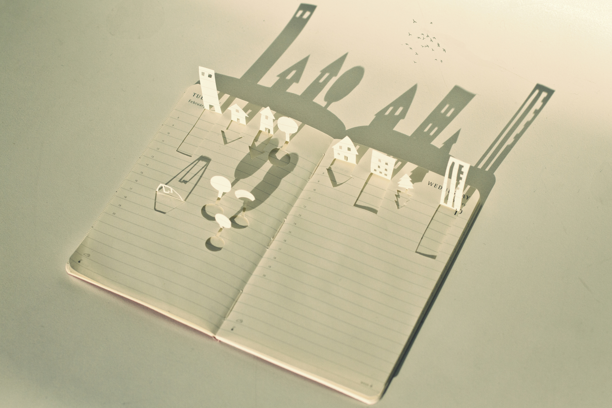 Small open book filled with delicate hand made paper cuttings depicting city scene which is lit by sunlight casting shadow of city on white background behind.