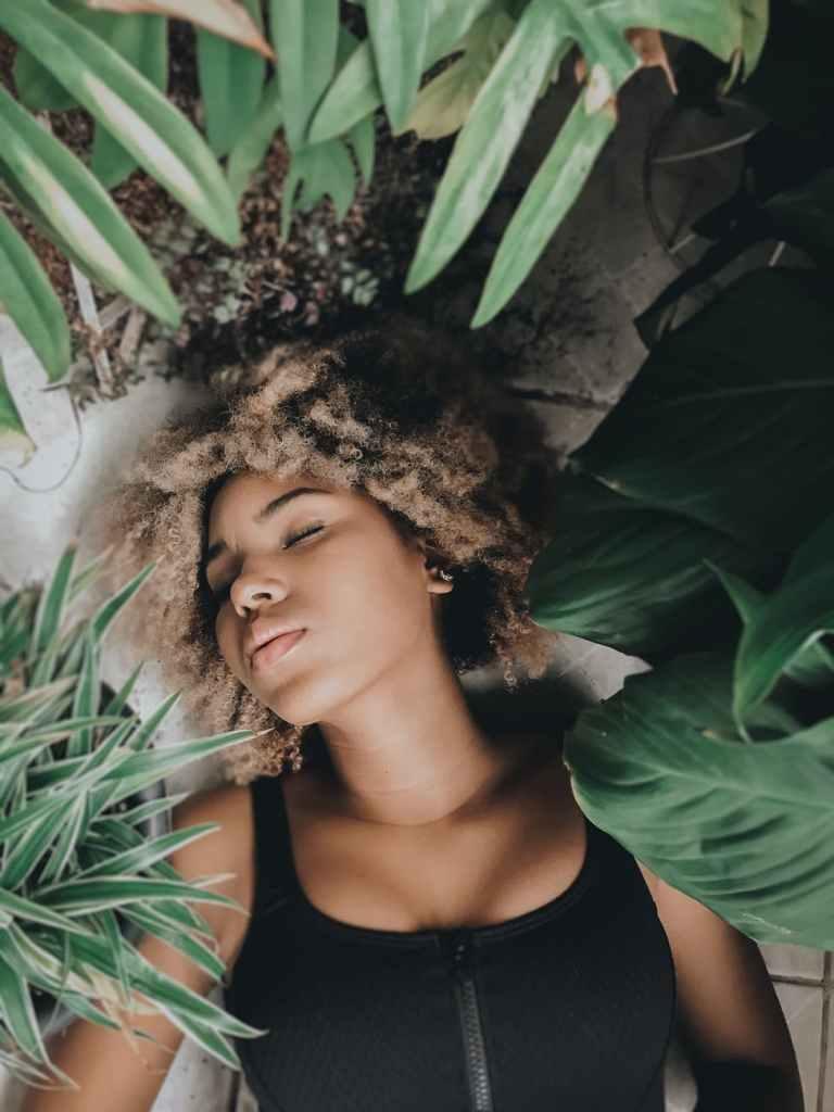 woman sleeping on floor among pot plants