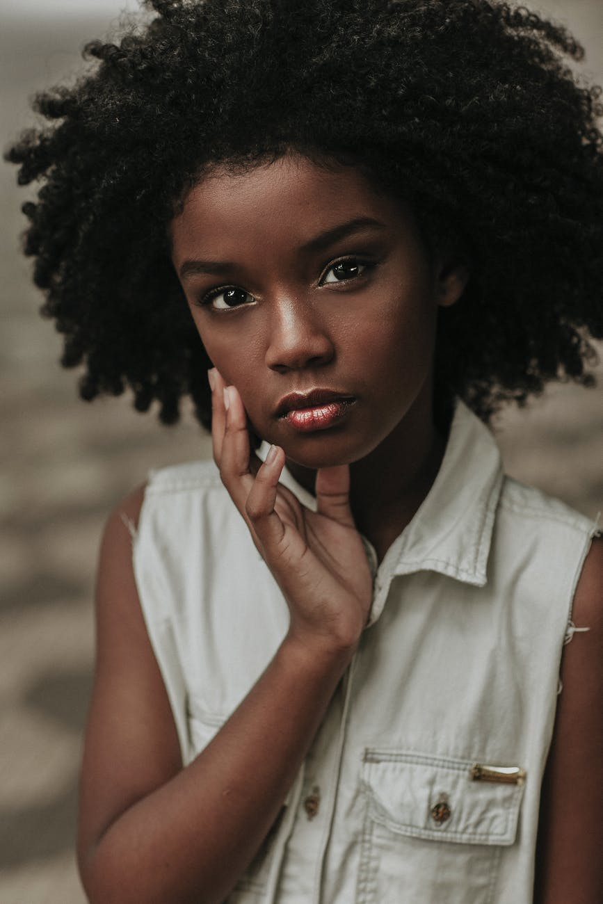 dreamy black teenage female touching face and looking at camera