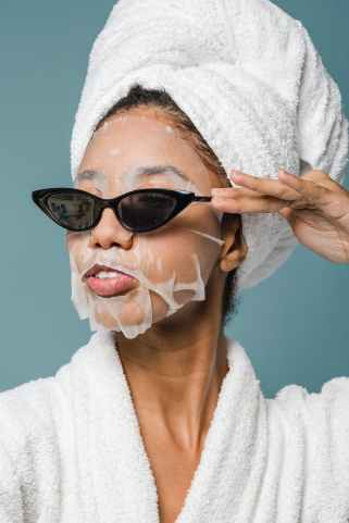 content young black woman wearing sunglasses during skin care treatment after bath codependancy