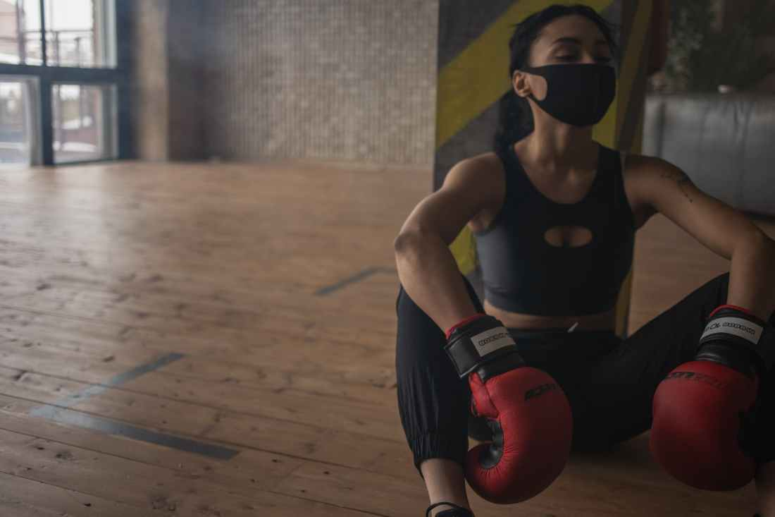 tired black woman in activewear and protective mask in gym