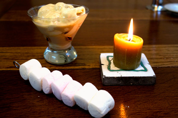 marshmallows on a skewer beside a candle and a sundae of vanilla icecream with baileys