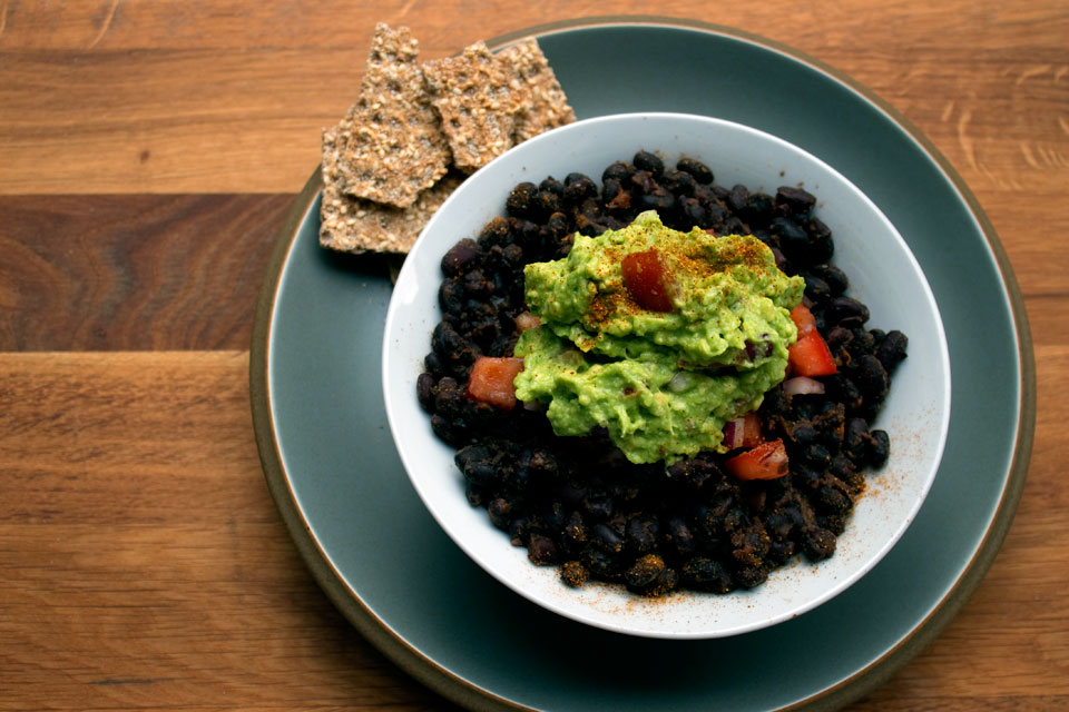 bowl of black beans topped with guacamole.