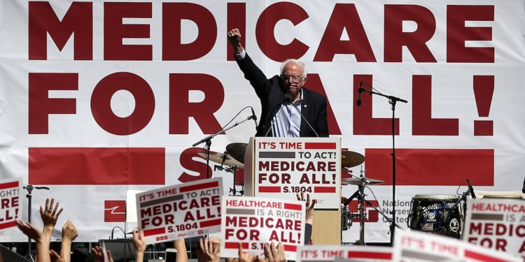 """Bernie Sanders delivering a speech, surrounded by """"Medicare for All"""" signs."""